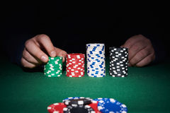 Poker chips on table with hands Stock Photos