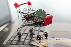 Poker chips in a trolley and euro banknotes on a computer. Online Gambling addiction concept. Poker chips in a trolley and euro banknotes on a computer .Online stock images