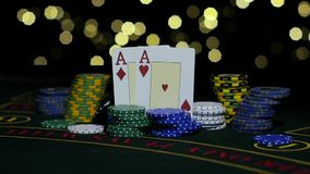 Poker Chips and Two Aces. Close up. Slow motion. Playing cards on poker table, pile of chips, winner's gain, combination of poker, pair of aces, rolling one stock video footage