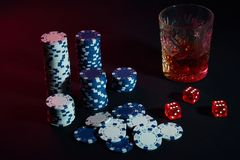 Poker chips and wine glass of cognac on dark table. Gambling. Poker chips and wine glass of cognac on dark table. Still life. The concept of gambling. Poker Royalty Free Stock Photo