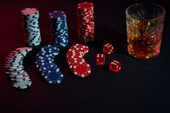 Poker chips and wine glass of cognac on dark table. Gambling. Poker chips and wine glass of cognac on dark table. Still life. The concept of gambling. Poker Royalty Free Stock Images