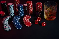 Poker chips and wine glass of cognac on dark table. Gambling. Poker chips and wine glass of cognac on dark table. Still life. The concept of gambling. Poker Royalty Free Stock Photography