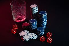 Poker chips and wine glass of cognac on dark table. Gambling Royalty Free Stock Photos