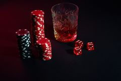 Poker chips and wine glass of cognac on dark table. Gambling. Poker chips and wine glass of cognac on dark table. Still life. The concept of gambling. Poker Royalty Free Stock Photos