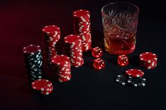 Poker chips and wine glass of cognac on dark table. Gambling. Poker chips and wine glass of cognac on dark table. Still life. The concept of gambling. Poker Stock Photography