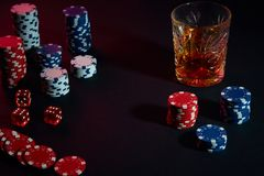 Poker chips and wine glass of cognac on dark table. Gambling. Poker chips and wine glass of cognac on dark table. Still life. The concept of gambling. Poker Stock Photos