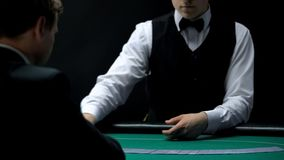Poker croupier dealing cards on green table for casino client, legal gambling. Stock photo royalty free stock images