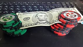 Poker & dollars. 5 dollars and poker chips on a laptop Stock Photos