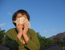 Poker face. Kid playing cards Royalty Free Stock Photos