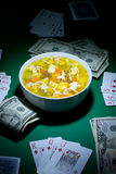Poker and food. Nice bowl of soup and some cash  is been played on cards Stock Photo