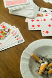 Poker full on brown table and butts in ashtray. Playing cards on brown table and smoking cigarettes Royalty Free Stock Photo