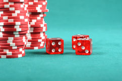 Red poker gambling chips on a green playing table Stock Image