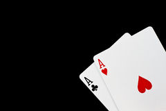 Poker game. A poker hand with 2 aces isolated on black stock images