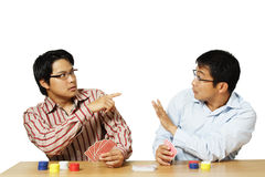 Poker game. An isolated shot of two men playing poker with one of them get caught for cheating royalty free stock photos