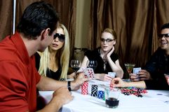 Poker game. Group of two couples, four attractive young people, playing poker, having a drink Royalty Free Stock Photography