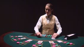 Poker game dealer hands out cards on a green table. Black background. Slow motion. Poker game dealer woman hands out cards on a green table. Black background stock footage