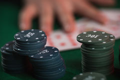 Poker game in men`s hands on green table.  Stock Image