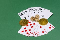 Poker game objects - game cards, dice and bitcoins on a green background royalty free stock photography