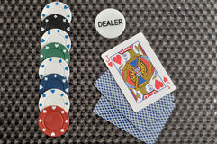 Poker game with poker chips, dealer chip and three cards Royalty Free Stock Images