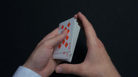 Poker game - shuffling cards. Man`s hands shuffing cards. Close up. Man`s hands shuffling playing cards. Dealer`s hands. Shuffling cards during a poker game 4K stock photo