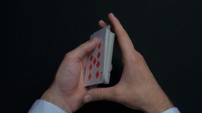 Poker game - shuffling cards. Man`s hands shuffing cards. Close up. Man`s hands shuffling playing cards. Dealer`s hands. Shuffling cards during a poker game 4K royalty free stock photography