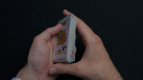 Poker game - shuffling cards. Man`s hands shuffing cards. Close up. Man`s hands shuffling playing cards. Dealer`s hands. Shuffling cards during a poker game 4K royalty free stock photo