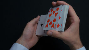 Poker game - shuffling cards. Man`s hands shuffing cards. Close up. Man`s hands shuffling playing cards. Dealer`s hands. Shuffling cards during a poker game 4K stock photography