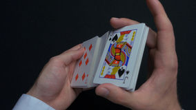 Poker game - shuffling cards. Man`s hands shuffing cards. Close up. Man`s hands shuffling playing cards. Dealer`s hands. Shuffling cards during a poker game 4K stock images