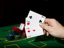 Poker on a green table background, man holding losing combination of cards Stock Images