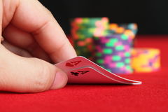 Poker hand. Image of a poker hand close up, pair of aces, with poker chips in the background on a red felt table Royalty Free Stock Photo