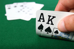 Poker Hand. Poker winning hand with Ace and King possible flush or straight, good hand suited spades against green table background stock photography