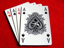 Poker hand 4 aces. A poker hand of 4 aces on a red felt poker table background stock photo