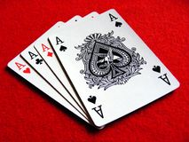 Poker hand 4 aces. A poker hand of 4 aces on a red felt poker table background stock photos