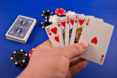 Poker Hand. A hand holding a royal flush with poker chips and a deck of cards in the background stock photo