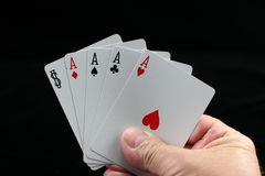 Poker hand. Poker hand of four aces & Joker on a black background Stock Photos