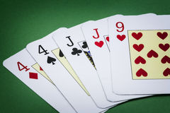 Poker hand call two pairs. Consisting of two pairs of cards of the number four, two pairs of cards of j and a letter from the nine of hearts green background Royalty Free Stock Photography