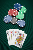 Poker hand Four of a Kind. Poker hand of five cards of Four of a Kind on a green table next to chips Royalty Free Stock Image