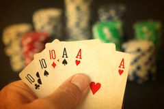 Poker hand with full house cards and jeton chips in close up on black backgrund - made like an old photo. Graph royalty free stock photos