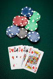 Poker hand Full House. Poker hand of five cards of Full House on a green table next to chips Stock Photos