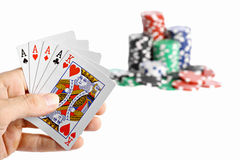 Poker Hand. A poker hand holding a four of a kind with poker chips in the background Stock Photography