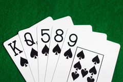 Poker hand of playing cards on green casino cloth Stock Photo