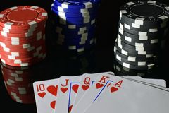 Poker hand royal flush and poker chips. Poker hand royal flush on black reflective board. Poker chips on background Stock Image