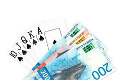 Poker cards mixed on the table. Poker hand royal flush in spades and some norwegian krone bank notes isolated on white background with copyspace stock images