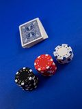 Poker Items. A deck of cards and poker chips on a blue background royalty free stock photos
