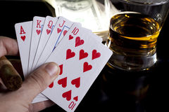 Poker night. Poker playing cards whiskey and some money on a table with reflection Royalty Free Stock Photo