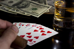 Poker night. Poker playing cards whiskey and some money on a table with reflection Royalty Free Stock Photos