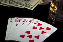 Poker night. Poker playing cards whiskey and some money on a table with reflection Royalty Free Stock Images