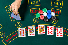 Poker play. Cards. Poker play. Chips in a player's hand.  top view. female hand lifts the cards to see Royalty Free Stock Image