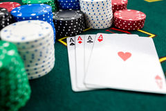 Poker play. Chips and cards. On the green table stock photo