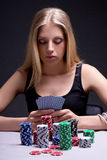 Poker player in casino with cards and chips Stock Image
